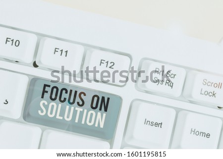 Conceptual hand writing showing Focus On Solution. Business photo showcasing Give full attention on dealing answer of the situation White pc keyboard with note paper above the white background.