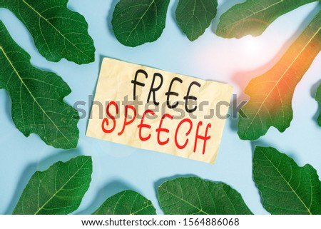 Conceptual hand writing showing Free Speech. Business photo showcasing the right of showing to express their opinions publicly Leaves surrounding notepaper above empty soft pastel table.