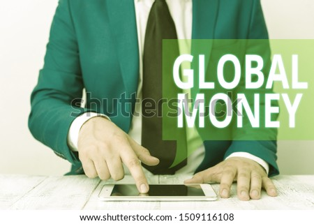 Conceptual hand writing showing Global Money. Business photo showcasing International finance World currency Transacted globally Businessman in blue suite with a tie holds lap top in hands. #1509116108