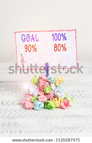 Conceptual hand writing showing Goal 100 Percent 90 Percent 80 Percent. Business photo text Percentage of your objectives fulfilment success level Reminder pile colored crumpled paper clothespin