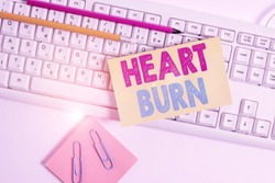 Conceptual hand writing showing Heart Burn. Business photo showcasing a burning sensation or pain in the throat from acid reflux White keyboard with note paper and clips on white background.