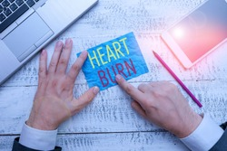 Conceptual hand writing showing Heart Burn. Business photo text a burning sensation or pain in the throat from acid reflux Hand hold note paper near writing equipment and smartphone.