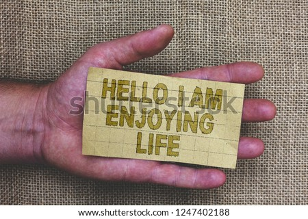 Conceptual hand writing showing Hello I Am Enjoying Life. Business photo showcasing Happy relaxed lifestyle Enjoy simple things Thick gray paper with words human hands jute sack background. #1247402188