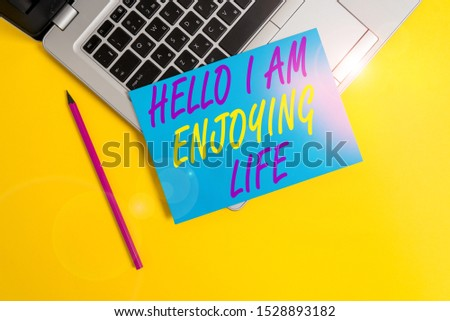 Conceptual hand writing showing Hello I Am Enjoying Life. Business photo showcasing Happy relaxed lifestyle Enjoy simple things Metallic laptop small paper sheet pencil colored background. #1528893182