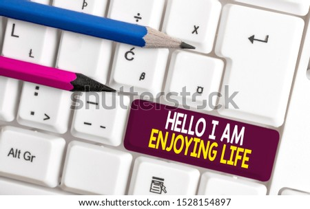 Conceptual hand writing showing Hello I Am Enjoying Life. Business photo text Happy relaxed lifestyle Enjoy simple things White pc keyboard with note paper above the white background. #1528154897