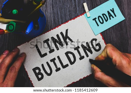 Conceptual hand writing showing Link Building. Business photo text SEO Term Exchange Links Acquire Hyperlinks Indexed Man holding marker paper clothespin reminder cup marker wood table. #1185412609