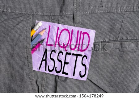 Conceptual hand writing showing Liquid Assets. Business photo text Cash and Bank Balances Market Liquidity Deferred Stock Writing equipment and purple note paper inside pocket of trousers. #1504178249