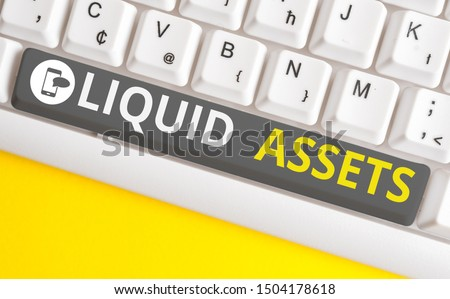 Conceptual hand writing showing Liquid Assets. Business photo text Cash and Bank Balances Market Liquidity Deferred Stock White pc keyboard with note paper above the white background. #1504178618