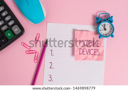 Conceptual hand writing showing Mobile Devices. Business photo showcasing A portable computing device like smartphone tablet computer Calculator clock mouse crushed note pencil color background. #1469898779