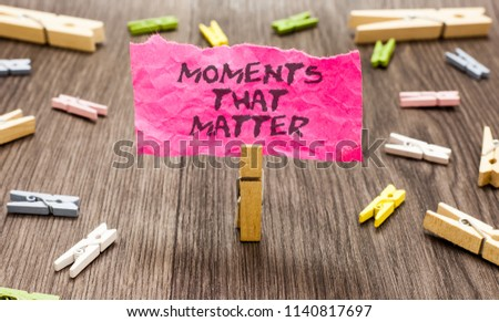 Conceptual hand writing showing Moments That Matter. Business photo showcasing Meaningful positive happy memorable important times Paperclip hold pink note with texts many clips wooden floor. #1140817697