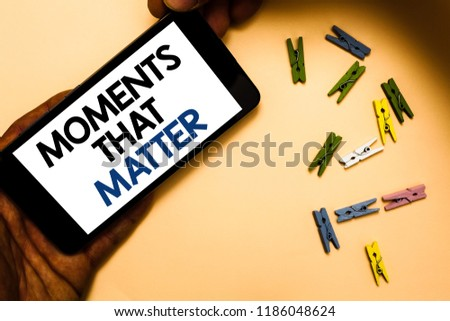 Conceptual hand writing showing Moments That Matter. Business photo text Meaningful positive happy memorable important times Hand holding iPhone with letters and paperclip peach color ground. #1186048624