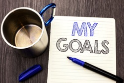 Conceptual hand writing showing My Goals. Business photo showcasing Goal Aim Strategy Determination Career Plan Objective Target Vision written on Notebook Paper wooden background Marker and Cup