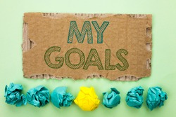 Conceptual hand writing showing My Goals. Business photo text Goal Aim Strategy Determination Career Plan Objective Target Vision written on Tear Cardboard on plain background Crumpled Paper Balls.