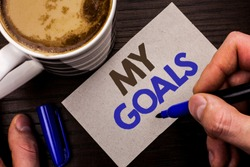 Conceptual hand writing showing My Goals. Business photo text Goal Aim Strategy Determination Career Plan Objective Target Vision written Man Holding Marker on Note Paper Wooden background Coffee.