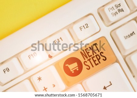 Conceptual hand writing showing Next Steps. Business photo showcasing numper of process going to be made after current one planning White pc keyboard with note paper above the white background. #1568705671