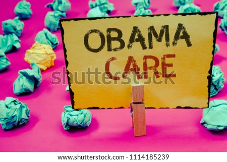 Conceptual hand writing showing Obama Care. Business photos showcasing Government Program of Insurance System Patient ProtectionClothespin hold holding Yellow paper ideas crumpled papers.