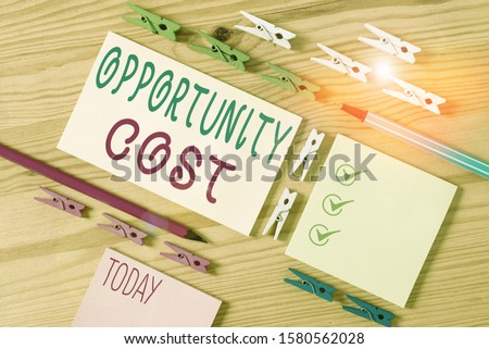 Conceptual hand writing showing Opportunity Cost. Business photo showcasing the price of the next best thing you could have done Colored crumpled papers wooden floor background clothespin.