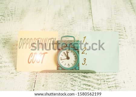 Conceptual hand writing showing Opportunity Cost. Business photo showcasing the price of the next best thing you could have done Mini blue clock standing above buffer wire between two paper.