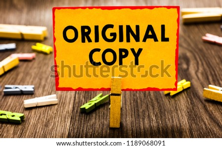 Conceptual hand writing showing Original Copy. Business photo showcasing Main Script Unprinted Branded Patented Master List Clothespin holding orange paper note clothespin wooden floor. #1189068091