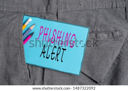 Conceptual hand writing showing Phishing Alert. Business photo showcasing aware to fraudulent attempt to obtain sensitive information Writing equipment and blue note paper in pocket of trousers.