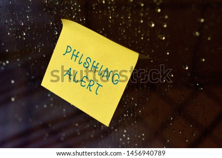 Conceptual hand writing showing Phishing Alert. Business photo text aware to fraudulent attempt to obtain sensitive information Square paper piece notation stick to textured glass window.