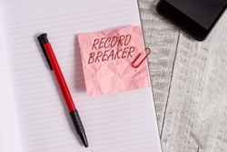 Conceptual hand writing showing Record Breaker. Business photo text someone or something that beats previous best result Wrinkle paper notebook and stationary placed on wooden background.