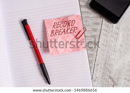 Conceptual hand writing showing Record Breaker. Business photo text someone or something that beats previous best result Wrinkle paper notebook and stationary placed on wooden background. #1469886656