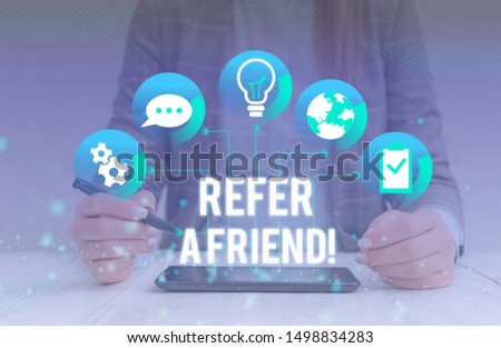 Conceptual hand writing showing Refer A Friend. Business photo showcasing direct someone to another or send him something like gift Female human wear formal work suit presenting smart device.