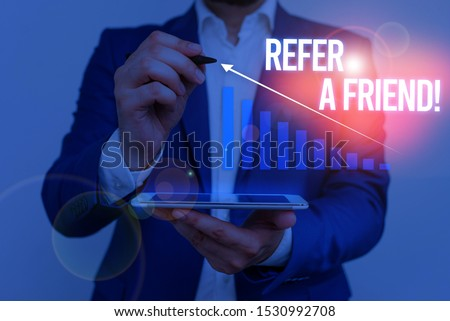 Conceptual hand writing showing Refer A Friend. Business photo showcasing direct someone to another or send him something like gift Male wear formal suit presenting presentation smart device.