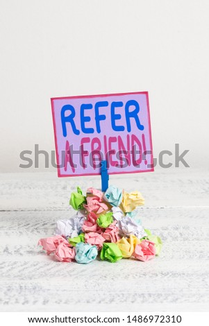 Conceptual hand writing showing Refer A Friend. Business photo text direct someone to another or send him something like gift Reminder pile colored crumpled paper clothespin wooden space.