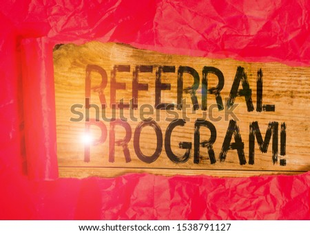 Conceptual hand writing showing Referral Program. Business photo showcasing internal recruitment method employed by organizations Cardboard which is torn placed above a wooden classic table. #1538791127