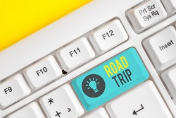 Conceptual hand writing showing Road Trip. Business photo showcasing Roaming around places with no definite or exact target location White pc keyboard with note paper above the white background.