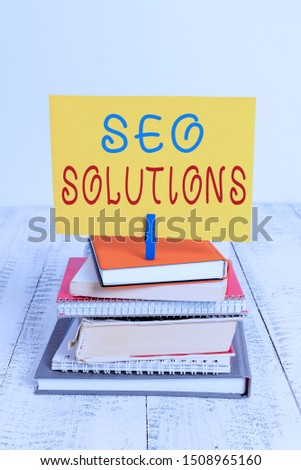 Conceptual hand writing showing Seo Solutions. Business photo showcasing Search Engine Result Page Increase Visitors by Rankings pile stacked books notebook pin color reminder white wooden. #1508965160