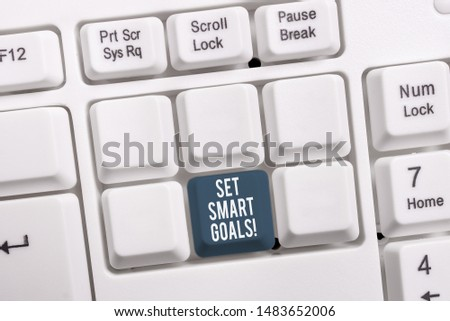 Conceptual hand writing showing Set Smart Goals. Business photo showcasing list to clarify your ideas focus efforts use time wisely White pc keyboard with note paper above the white background.