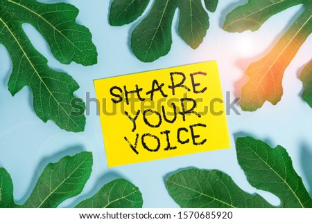Conceptual hand writing showing Share Your Voice. Business photo showcasing asking employee or member to give his opinion or suggestion Leaves surrounding notepaper above empty soft pastel table.