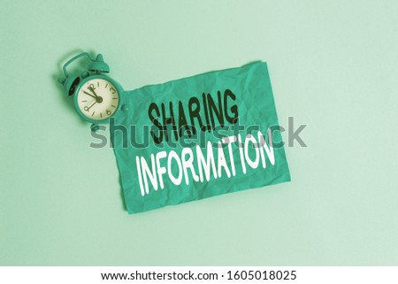 Conceptual hand writing showing Sharing Information. Business photo showcasing exchange of data between various organizations Metal vintage alarm clock crush sheet sky colored background.