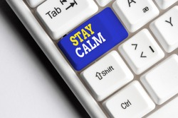 Conceptual hand writing showing Stay Calm. Business photo showcasing Maintain in a state of motion smoothly even under pressure White pc keyboard with note paper above the white background.