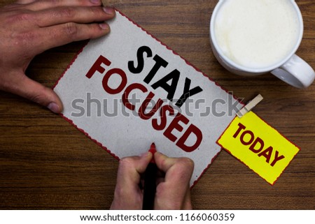 Conceptual hand writing showing Stay Focused. Business photo text Be attentive Concentrate Prioritize the task Avoid distractions Man holding marker notebook reminder wooden table cup coffee.