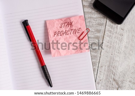 Conceptual hand writing showing Stay Proactive. Business photo text Taking own decision to go ahead of anticipated events Wrinkle paper notebook and stationary placed on wooden background. #1469886665