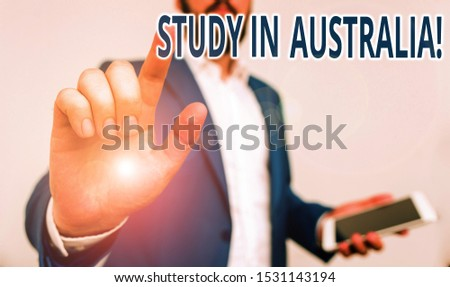 Conceptual hand writing showing Study In Australia. Business photo showcasing going into foreign country order complete your studies Businessman pointing with pen in empty copy space.