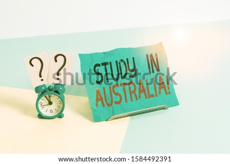 Conceptual hand writing showing Study In Australia. Business photo showcasing going into foreign country order complete your studies Alarm clock beside a Paper sheet placed on pastel backdrop.