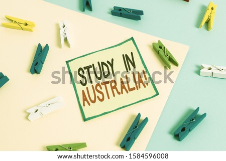 Conceptual hand writing showing Study In Australia. Business photo showcasing going into foreign country order complete your studies Colored clothespin paper reminder with yellowblue background.