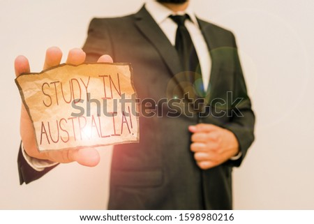 Conceptual hand writing showing Study In Australia. Business photo text going into foreign country order complete your studies Male human wear formal work suit with office look hold book.