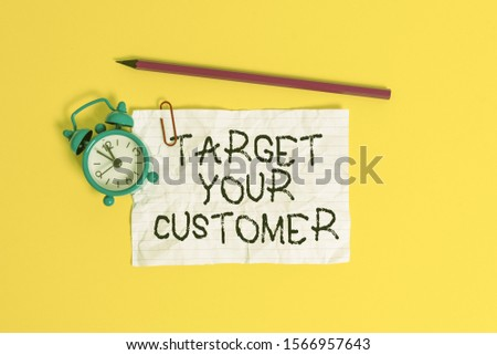 Conceptual hand writing showing Target Your Customer. Business photo showcasing Tailor Marketing Pitch Defining Potential Consumers Metal alarm clock ccrushed sheet pencil colored background.