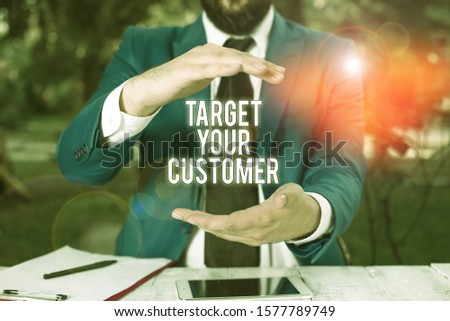Conceptual hand writing showing Target Your Customer. Business photo showcasing Tailor Marketing Pitch Defining Potential Consumers Man in front of table. Mobile phone and notes on the table.