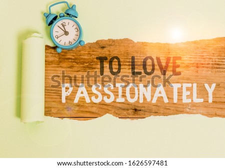 Conceptual hand writing showing To Love Passionately. Business photo text Strong feeling for someone or something else Affection Alarm clock and torn cardboard on a wooden classic table backdrop.
