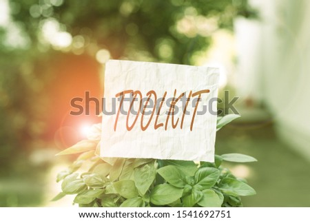 Conceptual hand writing showing Toolkit. Business photo text set of tools kept in a bag or box and used for a particular purpose Plain paper attached to stick and placed in the grassy land. #1541692751