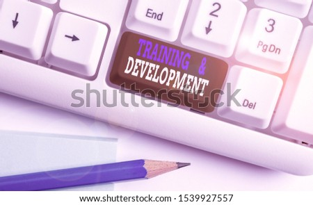 Conceptual hand writing showing Training And Development. Business photo text learn specific knowledge to improve perforanalysisce White pc keyboard with note paper above the white background.