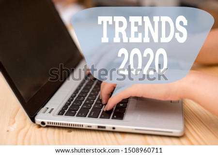 Conceptual hand writing showing Trends 2020. Business photo showcasing Upcoming year prevailing tendency Widely Discussed Online woman with laptop smartphone and office supplies technology.