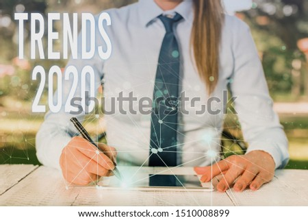 Conceptual hand writing showing Trends 2020. Business photo showcasing Upcoming year prevailing tendency Widely Discussed Online Female human wear formal work suit presenting smart device.